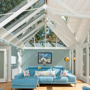 Cette image montre une véranda traditionnelle avec un sol en bois clair et un plafond en verre.