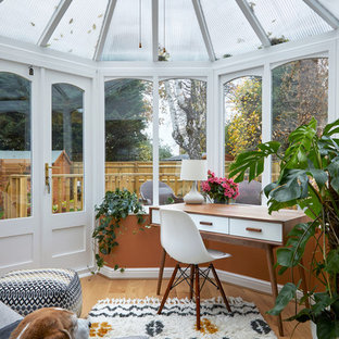 Photo of a traditional conservatory in London with light hardwood flooring, a glass ceiling and beige floors.