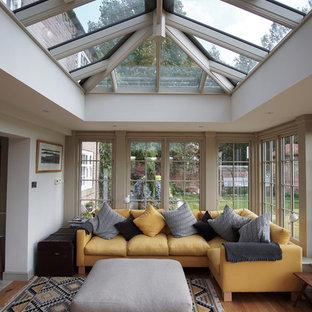 Inspiration pour une véranda traditionnelle avec un sol en bois clair, un plafond en verre et un sol marron.