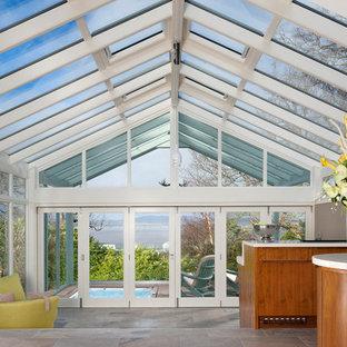 Idées déco pour une grand véranda moderne avec un sol en travertin, un sol gris et un plafond en verre.