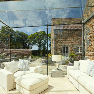Country conservatory in Channel Islands with a glass ceiling and beige floors.