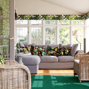Medium sized classic conservatory in London with a standard ceiling, medium hardwood flooring and brown floors.