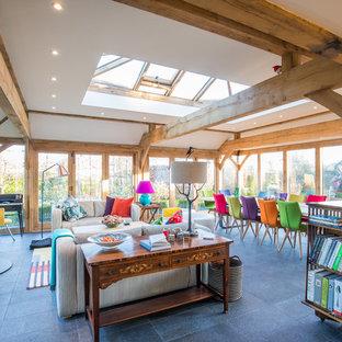 Foto di una grande veranda eclettica con stufa a legna, lucernario, cornice del camino in metallo e pavimento grigio