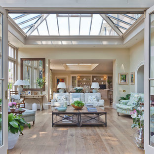 This is an example of a large traditional conservatory in Other with light hardwood flooring, no fireplace, a glass ceiling and beige floors.