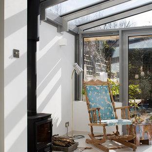 Ispirazione per una veranda scandinava di medie dimensioni con pavimento in gres porcellanato, stufa a legna, cornice del camino in pietra, soffitto in vetro e pavimento bianco