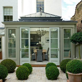 This is an example of a medium sized traditional conservatory in London with a glass ceiling.