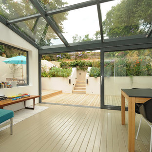 Design ideas for a retro conservatory in London with painted wood flooring, beige floors and a glass ceiling.
