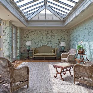 Klassisk inredning av ett stort uterum, med mellanmörkt trägolv och glastak