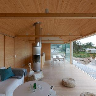 Immagine di un'ampia veranda scandinava con parquet chiaro e camino classico