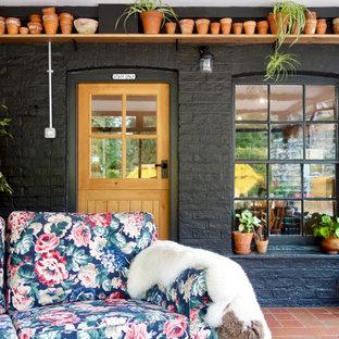 Inspiration pour une véranda chalet de taille moyenne avec un sol en carreau de terre cuite, aucune cheminée, un plafond standard et un sol rouge.