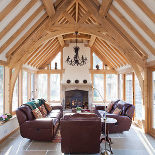 This is an example of a country conservatory in Other with a wood burning stove, grey floors and a standard ceiling.