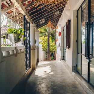 Idée de décoration pour un couloir ethnique avec un mur blanc, béton au sol et un sol gris.