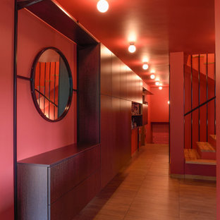 Photo of a large midcentury hallway in London with light hardwood floors, brown floor and red walls.