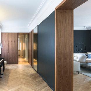 Idées déco pour un grand couloir contemporain avec un mur noir et un sol en bois clair.