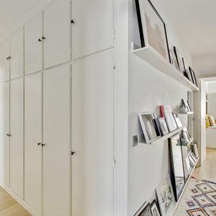 Idée de décoration pour un couloir design avec un mur blanc, un sol en bois clair et un sol beige.