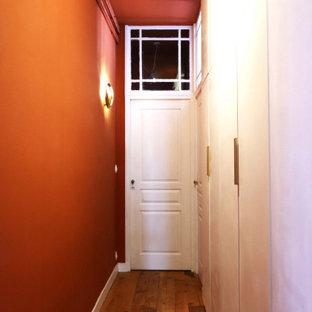 Inredning av en klassisk mellanstor hall, med röda väggar, ljust trägolv och beiget golv