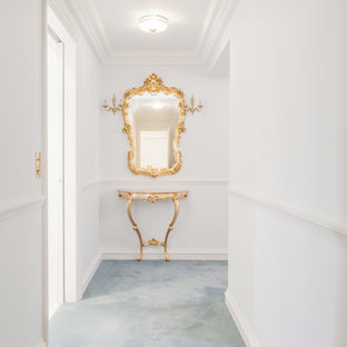 Exempel på en mellanstor klassisk hall, med vita väggar, heltäckningsmatta och blått golv