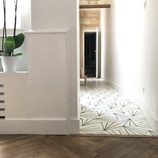 Inspiration for a mid-sized contemporary terra-cotta floor and white floor hallway remodel in Bordeaux with white walls