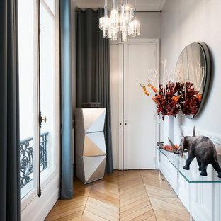 Réalisation d'un couloir bohème de taille moyenne avec un mur gris et un sol en bois brun.