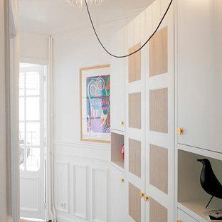 Inspiration pour un couloir bohème avec un mur blanc et un sol en bois clair.