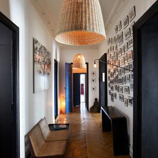 Idée de décoration pour un grand couloir design avec un mur blanc et un sol en bois brun.