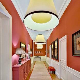 パリの巨大なトランジショナルスタイルのおしゃれな廊下 (オレンジの壁、無垢フローリング) の写真