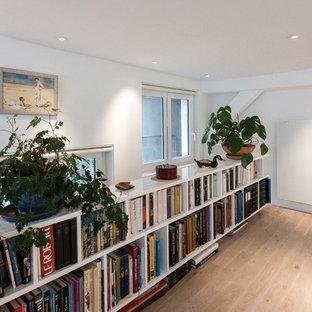 Cette photo montre un grand couloir tendance avec un mur blanc et un sol en bois clair.