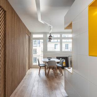 Idée de décoration pour un couloir design avec un mur jaune et un sol en bois clair.