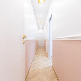Cette photo montre un couloir tendance de taille moyenne avec un mur rose, un sol en bois clair et un sol beige.