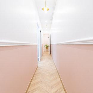 パリの中くらいのコンテンポラリースタイルのおしゃれな廊下 (ピンクの壁、淡色無垢フローリング、ベージュの床) の写真