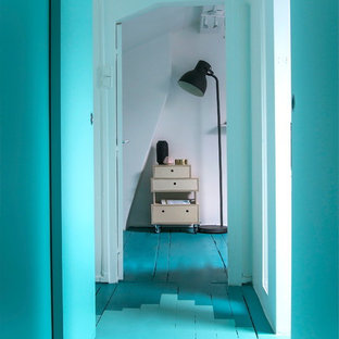 Foto på en mellanstor minimalistisk hall, med blå väggar och målat trägolv
