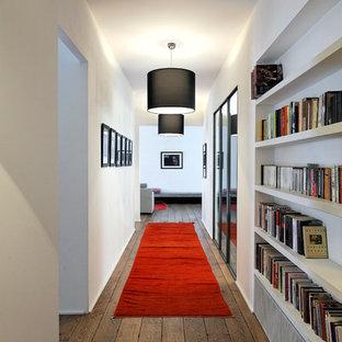 Cette image montre un grand couloir avec un mur blanc et un sol en bois brun.