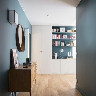Exemple d'un couloir tendance avec un mur bleu, un sol en bois clair et un sol beige.