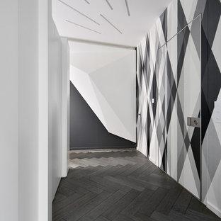 Foto på en mellanstor funkis hall, med flerfärgade väggar och mörkt trägolv
