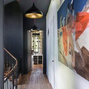 Idées déco pour un grand couloir éclectique avec un sol marron, un mur noir et un sol en bois brun.