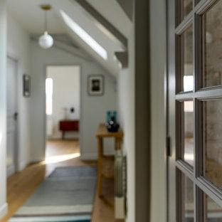 Inspiration för stora moderna hallar, med vita väggar, ljust trägolv och beiget golv