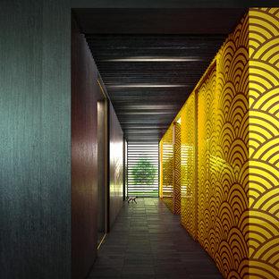 Aménagement d'un grand couloir contemporain avec un mur jaune et un sol en carrelage de céramique.