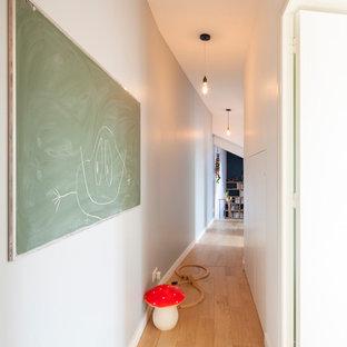 Idée de décoration pour un couloir design de taille moyenne avec un mur blanc et un sol en bois clair.