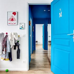Idée de décoration pour un couloir design de taille moyenne avec un mur bleu, un sol en bois clair et un sol beige.