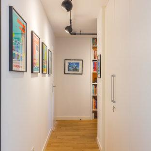 Réalisation d'un couloir vintage avec un mur blanc, un sol en bois brun et un sol marron.