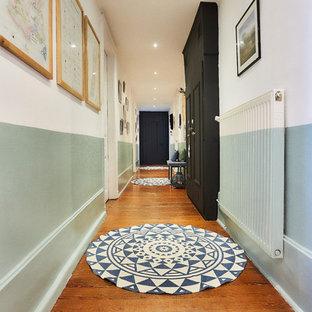 Exemple d'un très grand couloir scandinave avec un mur blanc, un sol en bois foncé et un sol marron.