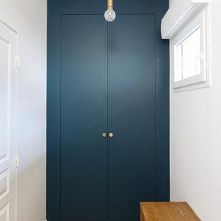 Cette photo montre un petit couloir moderne avec un mur bleu, un sol en bois clair et un sol beige.