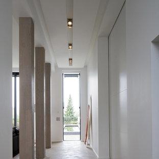 Idées déco pour un grand couloir contemporain avec un mur blanc et béton au sol.