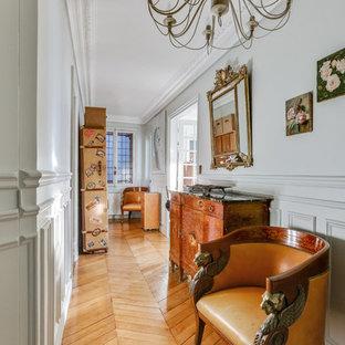 Idées déco pour un couloir classique avec un mur blanc, un sol en bois brun et un sol marron.