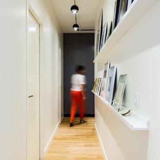 Exempel på en mellanstor modern hall, med vita väggar och ljust trägolv