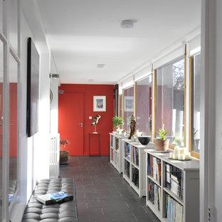 Cette image montre un grand couloir design avec un mur blanc et un sol en ardoise.