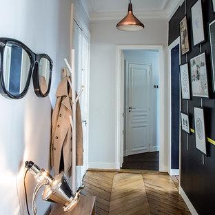 Aménagement d'un couloir éclectique de taille moyenne avec un mur blanc et un sol en bois brun.