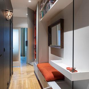 Réalisation d'un couloir design avec un mur gris, un sol en bois clair et un sol beige.