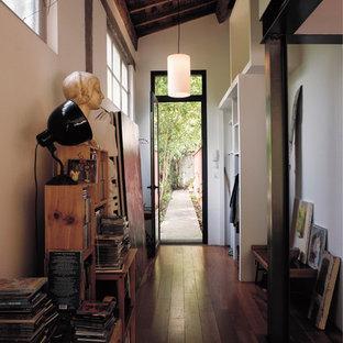 Réalisation d'un couloir bohème de taille moyenne avec un mur blanc et un sol en bois foncé.