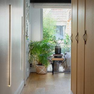 Ispirazione per un ingresso o corridoio industriale di medie dimensioni con pareti bianche, parquet chiaro, pavimento beige, travi a vista e pareti in mattoni